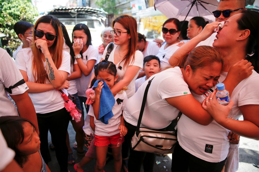 The wife and other relatives of Florjohn Cruz, who was killed in a police drugs buy-bust operation, cry as his coffin leaves their home for his funeral in Manila, Philippines. Photo by REUTERS/Damir Sagolj