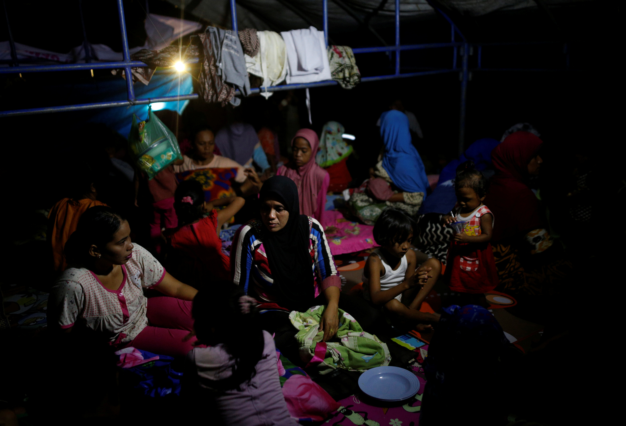People prepare to spend the night in a makeshift outdoor shelter following a strong earthquake near Meureudu, Pidie Jaya, Aceh province, Indonesia December 8, 2016. Photo By Darren Whiteside/Reuters