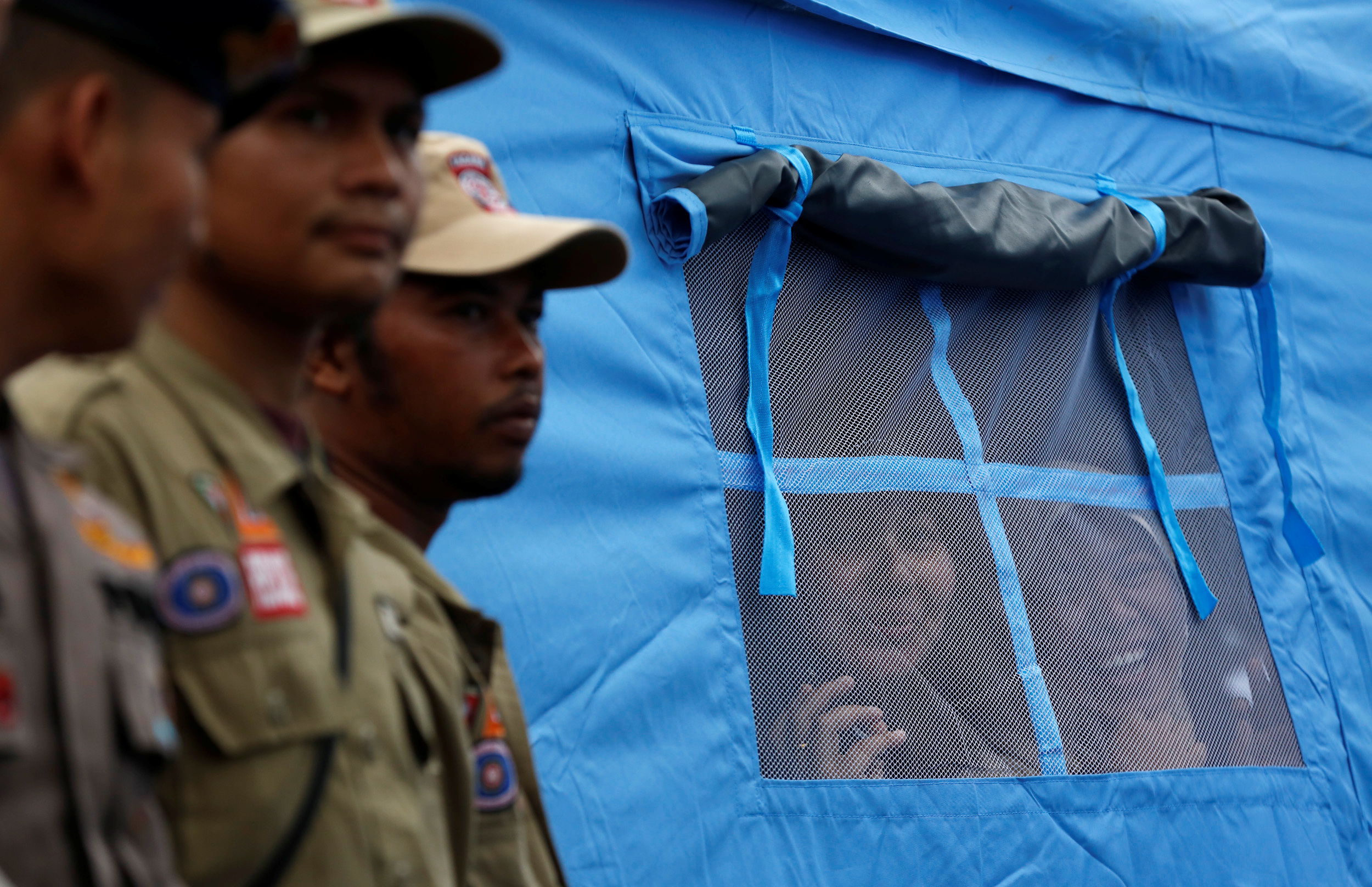 Women look out from a tent while waiting for Indonesian President Joko Widodo to walk by on the grounds of a collapsed mosque following this week's earthquake in Pidie Jaya, Aceh province, Indonesia December 9, 2016. Photo By Darren Whiteside/Reuters