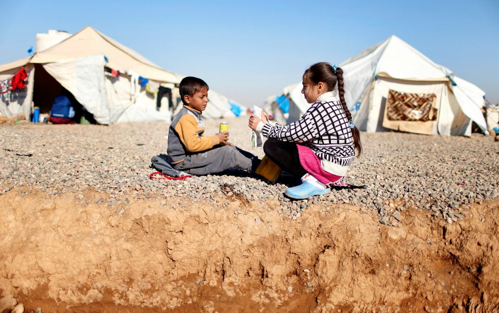 An Iraqi girl displaced by the fighting in Mosul teaches her brother in a camp on Dec. 9. Photo by Ahmed Jadallah/Reuters