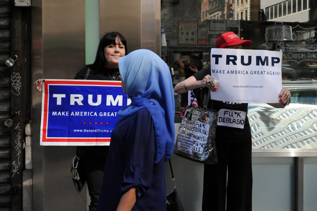 A woman wearing a Muslim headscarf walks past people holding Republican presidential nominee Donald Trump signs before the annual Muslim Day Parade in the Manhattan in September. Photo by Stephanie Keith/Reuters