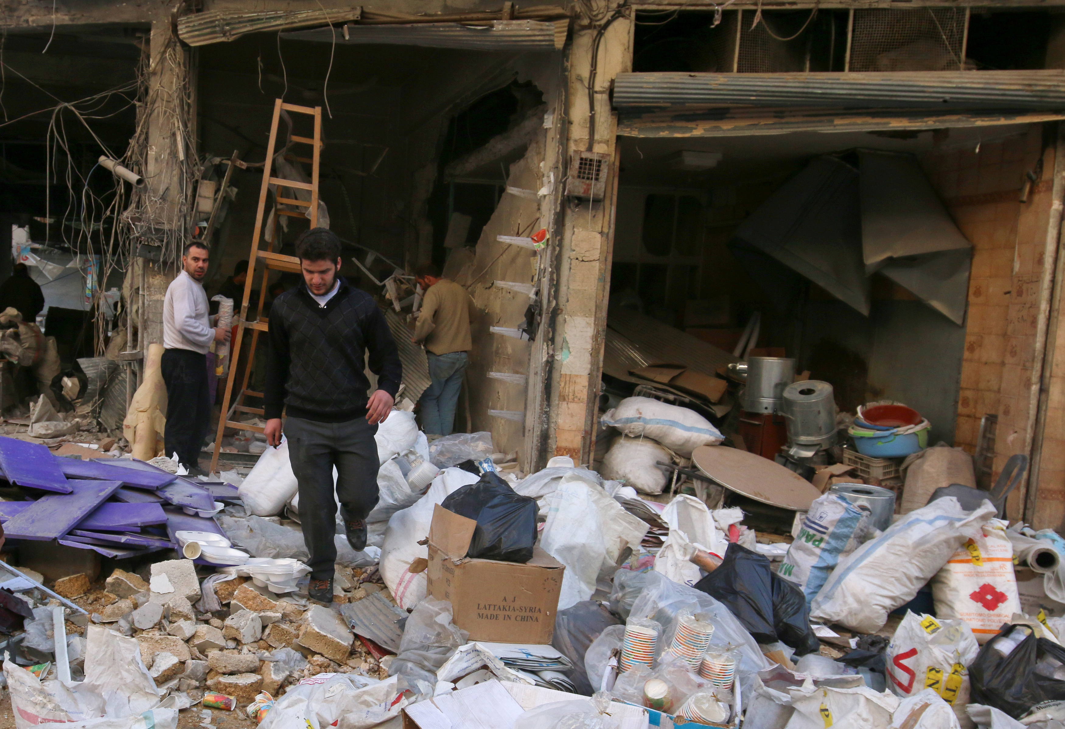 Men salvage belongings from their damaged shops at a site hit on Nov. 16 by airstrikes in the rebel held al-Shaar neighborhood of Aleppo. Photo by Abdalrhman Ismail/Reuters