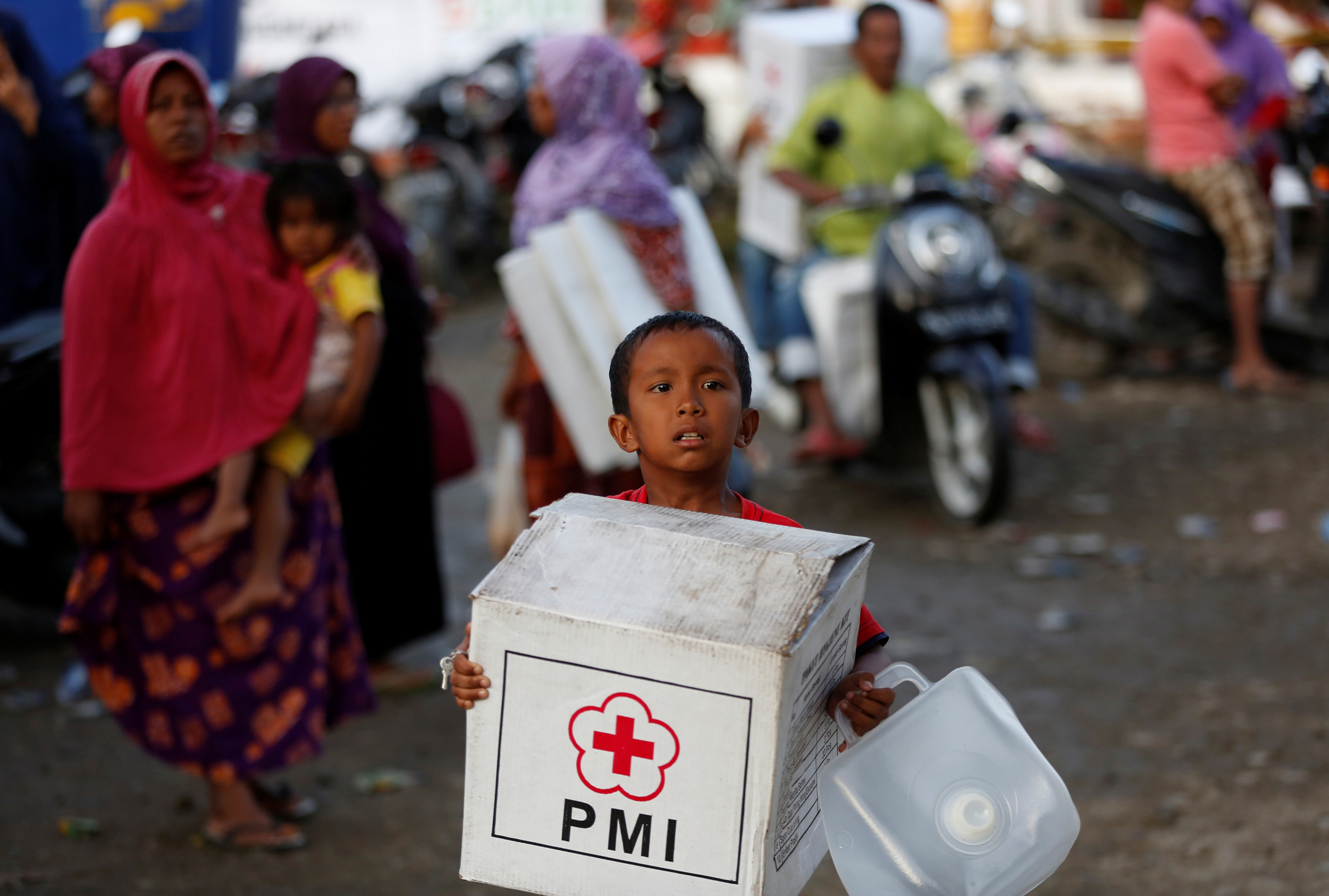 A boy carrying an aid package leaves a temporary shelter at a mosque following this week's strong earthquake in Meureudu, Pidie Jaya, Aceh province, Indonesia December 10, 2016. Photo By Darren Whiteside/Reuters