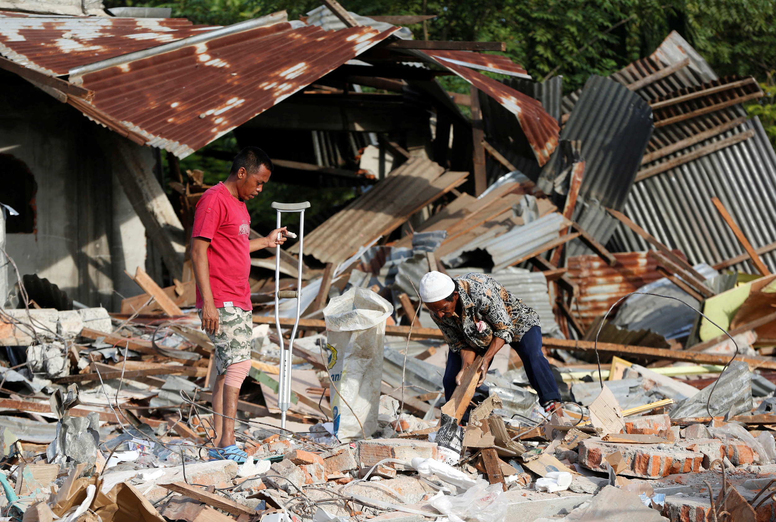 Men look for items to salvage from a building which collapsed following this week's strong earthquake in Pidie Jaya, Aceh province, Indonesia, December 10, 2016. Photo By Darren Whiteside/Reuters