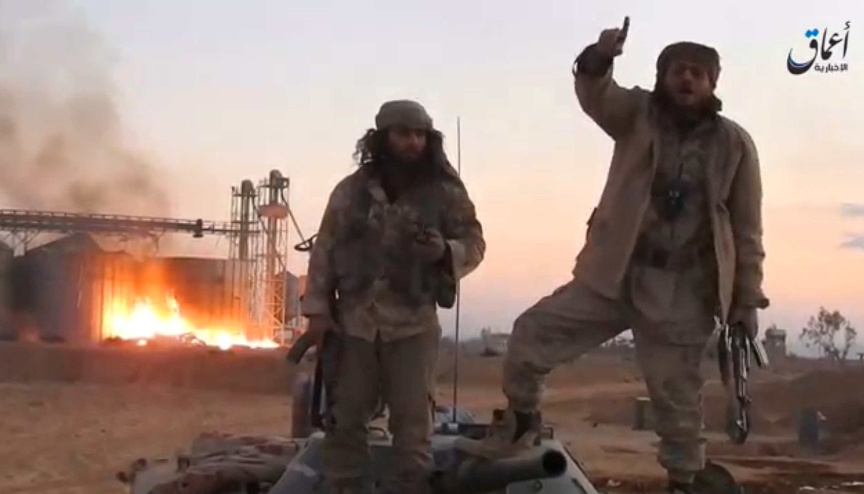 A still image taken from a video released by Islamic State-affiliated Amaq news agency, said to be in Palmyra, on December 11, 2016, purports to show Islamic State fighters in front of silos on fire and said to have been taken over by them. Handout via REUTERS