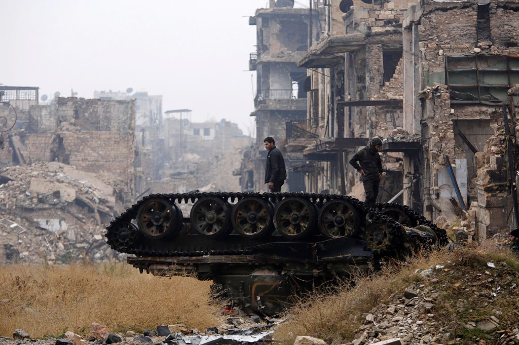 Forces loyal to Syria's President Bashar al-Assad stand atop a damaged tank near Umayyad mosque, in the government-controlled area of Aleppo, during a media tour on Dec. 13. Photo by Omar Sanadiki/Reuters
