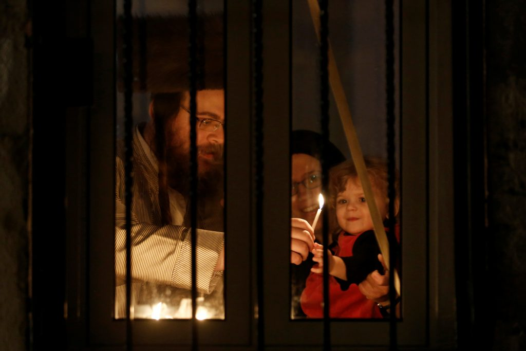 An ultra-orthodox Jewish family lights a candle on the first night of the holiday of Hanukkah in Jerusalem's Mea Shearim neighbourhood December 24, 2016. REUTERS/Amir Cohen - RTX2WDVL