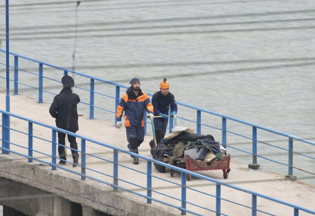 Russian Emergencies Ministry members push a cart with remains of Russian military Tu-154 plane which crashed into the Black Sea, at a quay in the Sochi suburb of Khosta, Russia, Russia December 25, 2016.  REUTERS/Yevgeny Reutov FOR EDITORIAL USE ONLY. NO RESALES. NO ARCHIVES. - RTX2WEVE