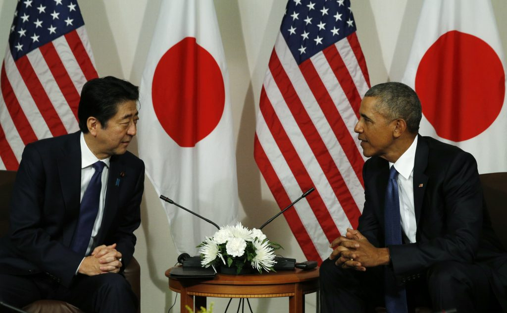 Japanese Prime Minister Shinzo Abe (L) talks with U.S. President Barack Obama during a meeting at Camp H.M. Smith in Aiea, Hawaii. Photo by Kevin Lamarque/Reuters