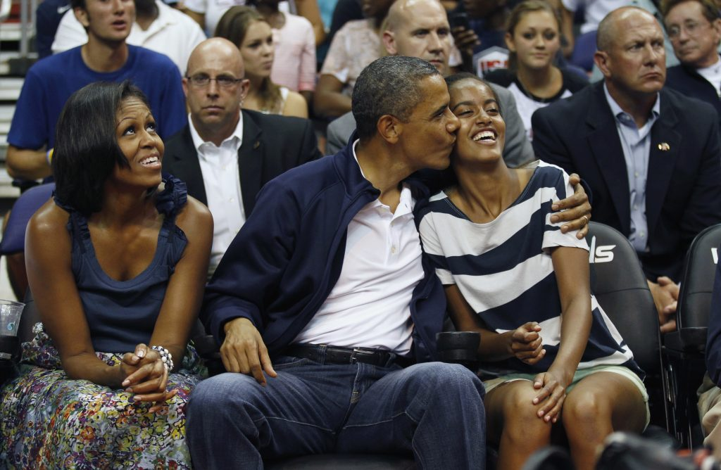 U.S. President Barack Obama kisses daughter Malia (R) as first lady Michelle Obama looks up as they attend the Olympic men's exhibition basketball game between Team USA and Brazil in Washington July 16, 2012. REUTERS/Kevin Lamarque (UNITED STATES - Tags: POLITICS SPORT BASKETBALL OLYMPICS) - RTR34ZY8