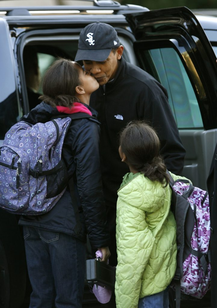 U.S. President-elect Barack Obama gets a kiss from his daughter Malia as his younger daughter Sasha watches upon being dropped off at their school in Chicago November 10, 2008. REUTERS/Kevin Lamarque (UNITED STATES) - RTXAGEA