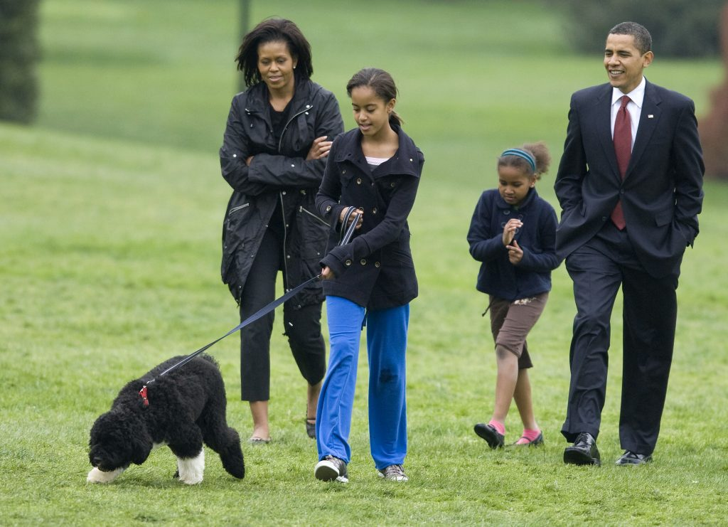 U.S. President Barack Obama (R) presents the first family's new Portuguese Water Dog puppy, Bo, on the South Lawn with his family at the White House in Washington April 14, 2009. With Obama are first lady Michelle Obama and daughters Malia (C) and Sasha. REUTERS/Larry Downing (UNITED STATES POLITICS ANIMALS SOCIETY IMAGE OF THE DAY TOP PICTURE) - RTXDZNB