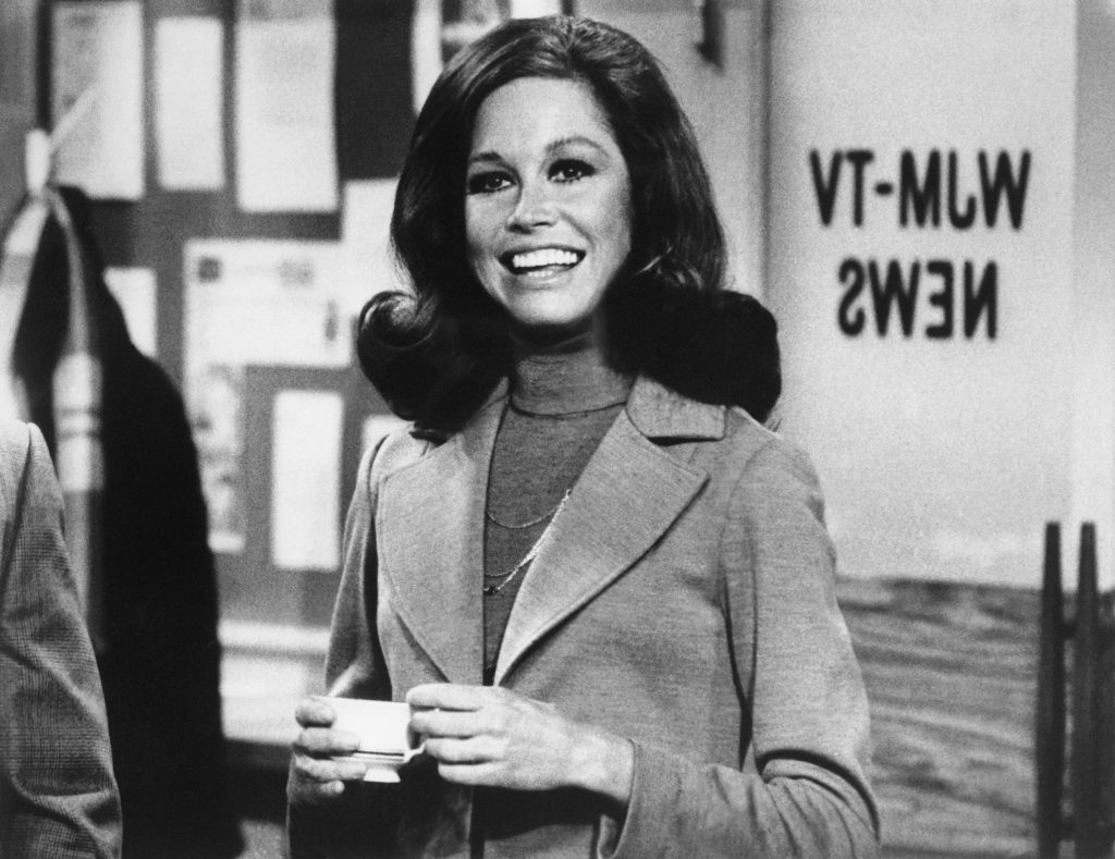 "Still from ""The Mary Tyler Moore Show"" showing Moore standing inside of the WJM-TV newsroom. Photo by Getty Images"