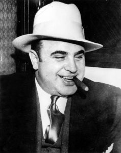 Al Capone smiles as he smokes a cigar on his way to Atlanta Federal Penitentiary after conviction for Federal Income Tax Evasion on  May 4, 1932, in Chicago. Photo by Popperfoto and Getty Images