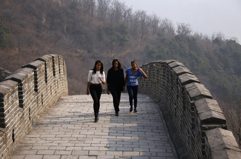 U.S. first lady Michelle Obama (C) walks with her daughters Sasha (R) and Malia as they visit the Mutianyu section of the Great Wall of China, in Beijing March 23, 2014. REUTERS/Petar Kujundzic (CHINA - Tags: POLITICS TRAVEL) - RTR3I778