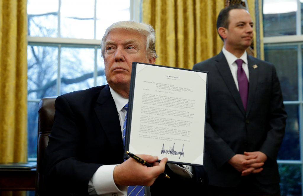 President Donald Trump holds up the executive order on the reinstatement of the Mexico City Policy after signing in the Oval Office of the White House in Washingtob, D.C., on  Jan. 23, 2017. At his side is White House Chief of Staff Reince Priebus. Photo by Kevin Lamarque/Reuters