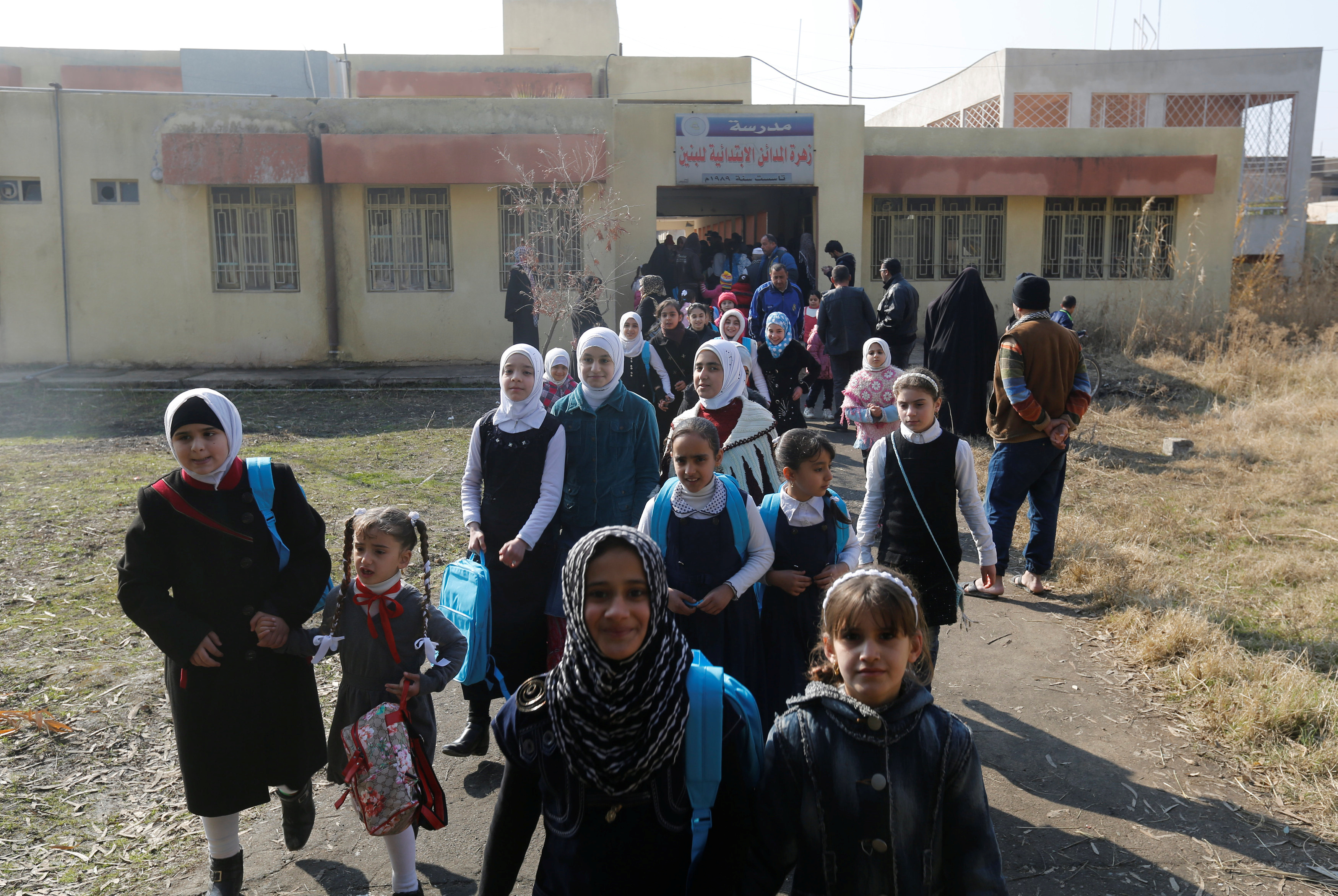 Students leave after registering for classes and getting new school bags in Mosul, Iraq on Jan. 23. Photo by Muhammad Hamed/Reuters