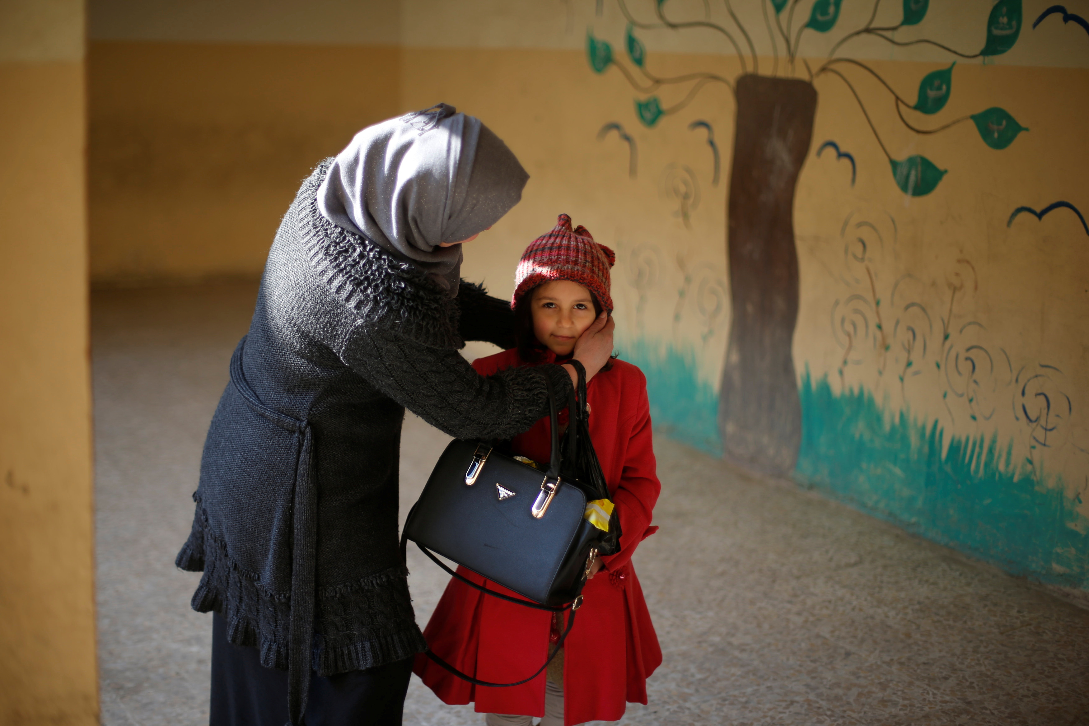 A mother adjusts her daughter's hat before she enters a classroom on Jan. 23. Photo by Muhammad Hamed/Reuters