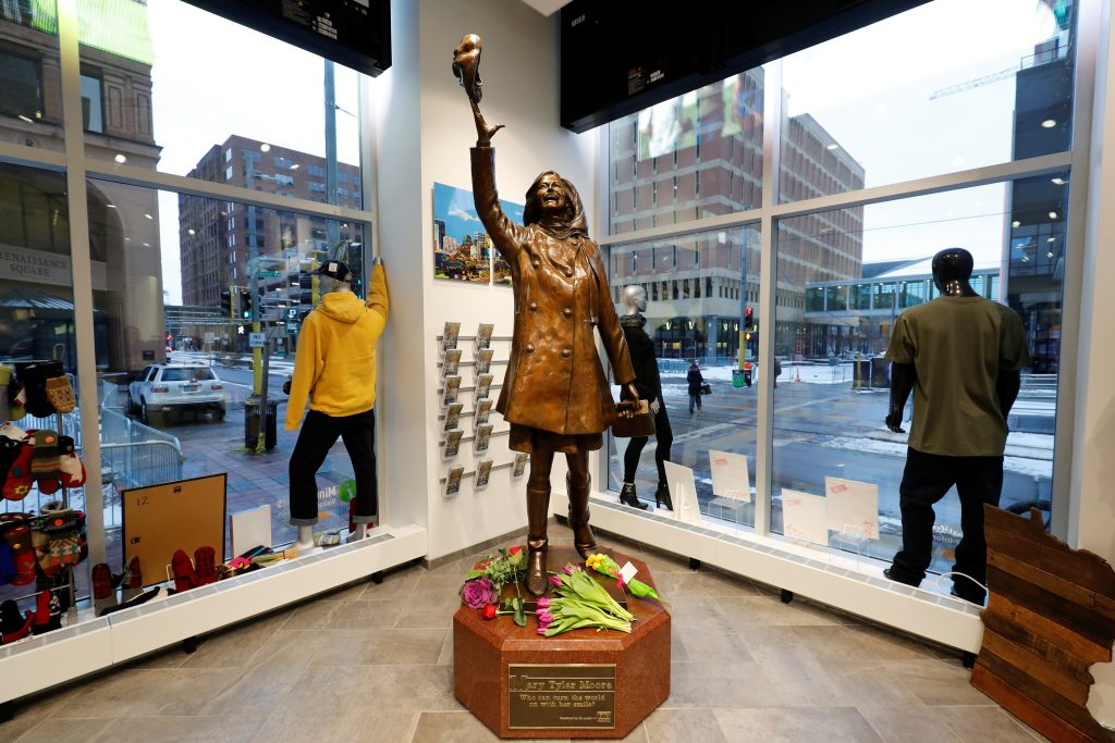"Flowers lay at a bronze sculpture depicting actress Mary Tyler Moore from the opening credits of the television sitcom ""The Mary Tyler Moore Show"" in Minneapolis, Minnesota. Photo by Adam Bettcher/Reuters"
