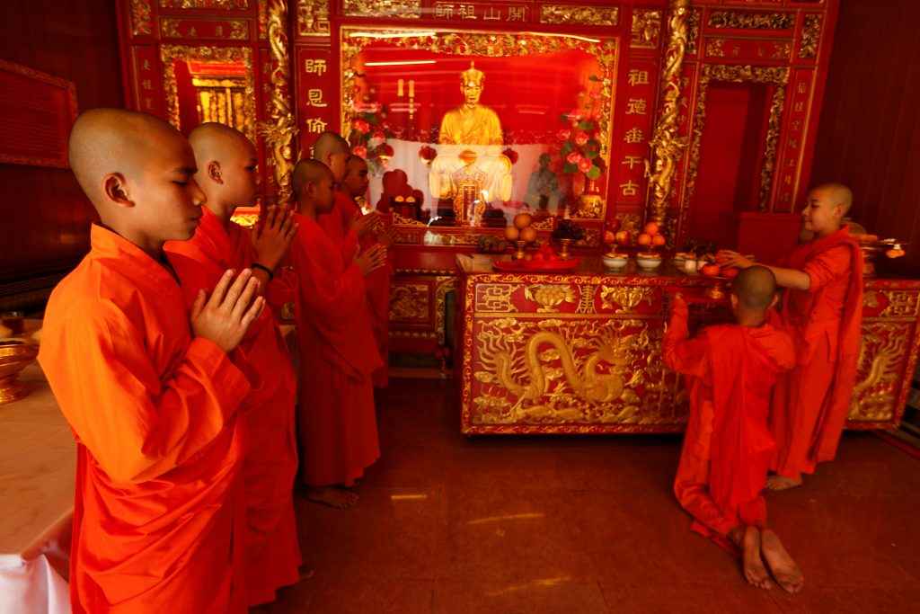 Buddhist monks pray inside a temple during the Lunar New Year eve celebration in Chinatown Bangkok, Thailand January 27 2017. REUTERS/Jorge Silva - RTSXL2Q