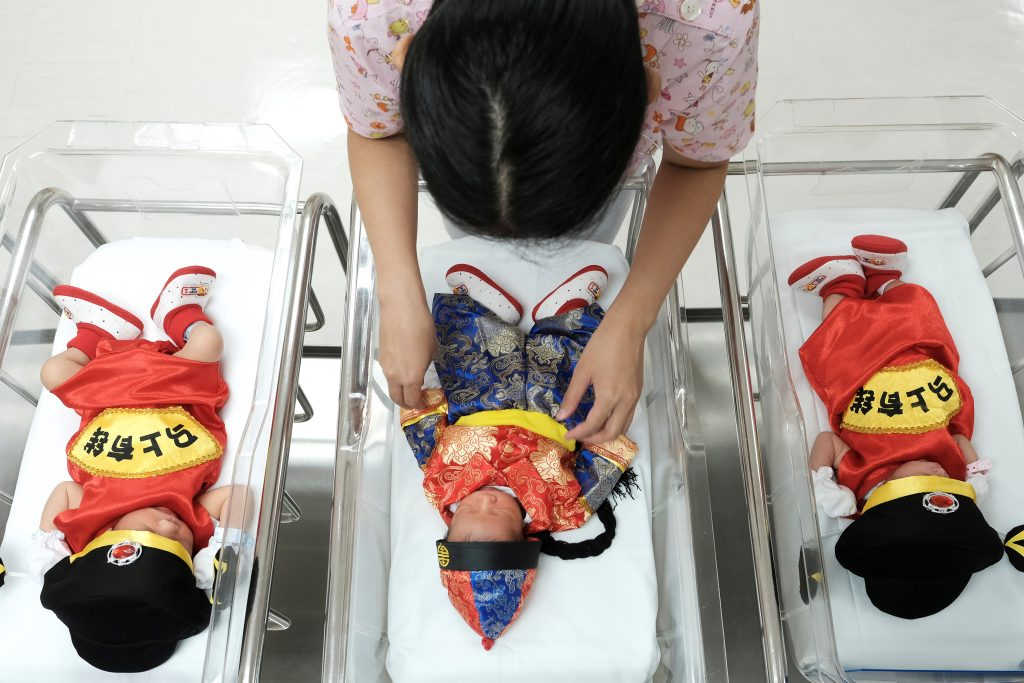 A nurse takes care of newborn babies wearing Chinese traditional costumes to celebrate the Chinese New Year at the nursery room of Paolo Chockchai 4 Hospital, in Bangkok, Thailand January 27, 2017. REUTERS/Athit Perawongmetha TPX IMAGES OF THE DAY - RTSXLDZ
