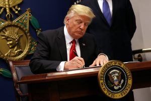 U.S. President Donald Trump signs an executive order to impose tighter vetting of travelers entering the United States, at the Pentagon in Washington, U.S., January 27, 2017. The executive order signed by Trump imposes a four-month travel ban on refugees entering the United States and a 90-day hold on travelers from Syria, Iran and five other Muslim-majority countries. Picture taken January 27, 2017. REUTERS/Carlos Barria - RTSXWMI