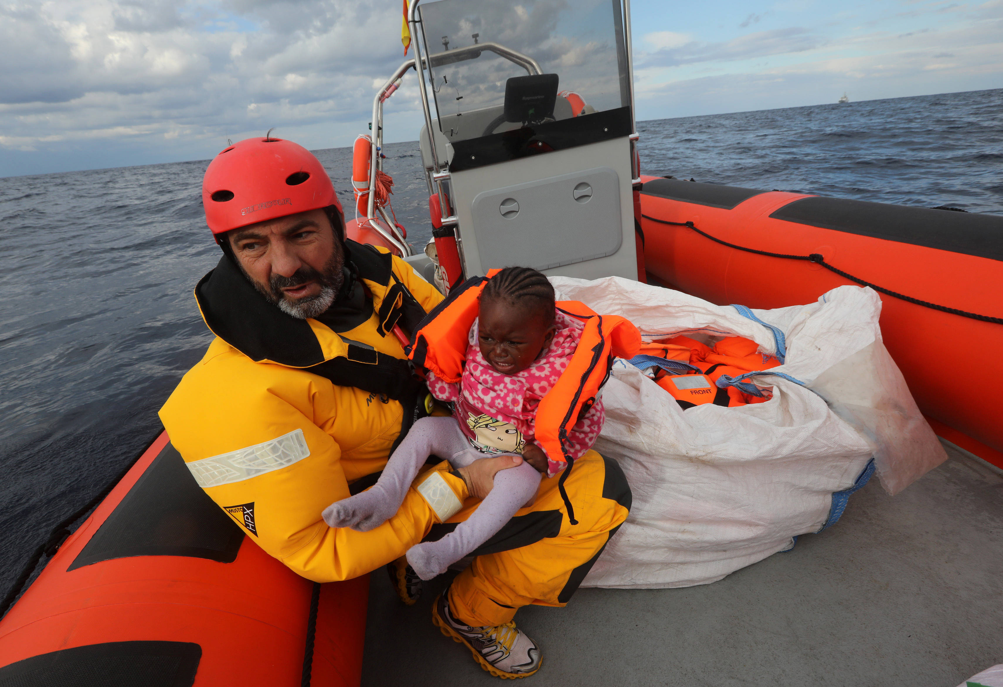 Oscar Camps, founder of Proactiva Open Arms, holds a baby removed from a raft that went adrift in the Mediterranean Sea. The group rescued all 112 migrants aboard. Photo by Yannis Behrakis/Reuters