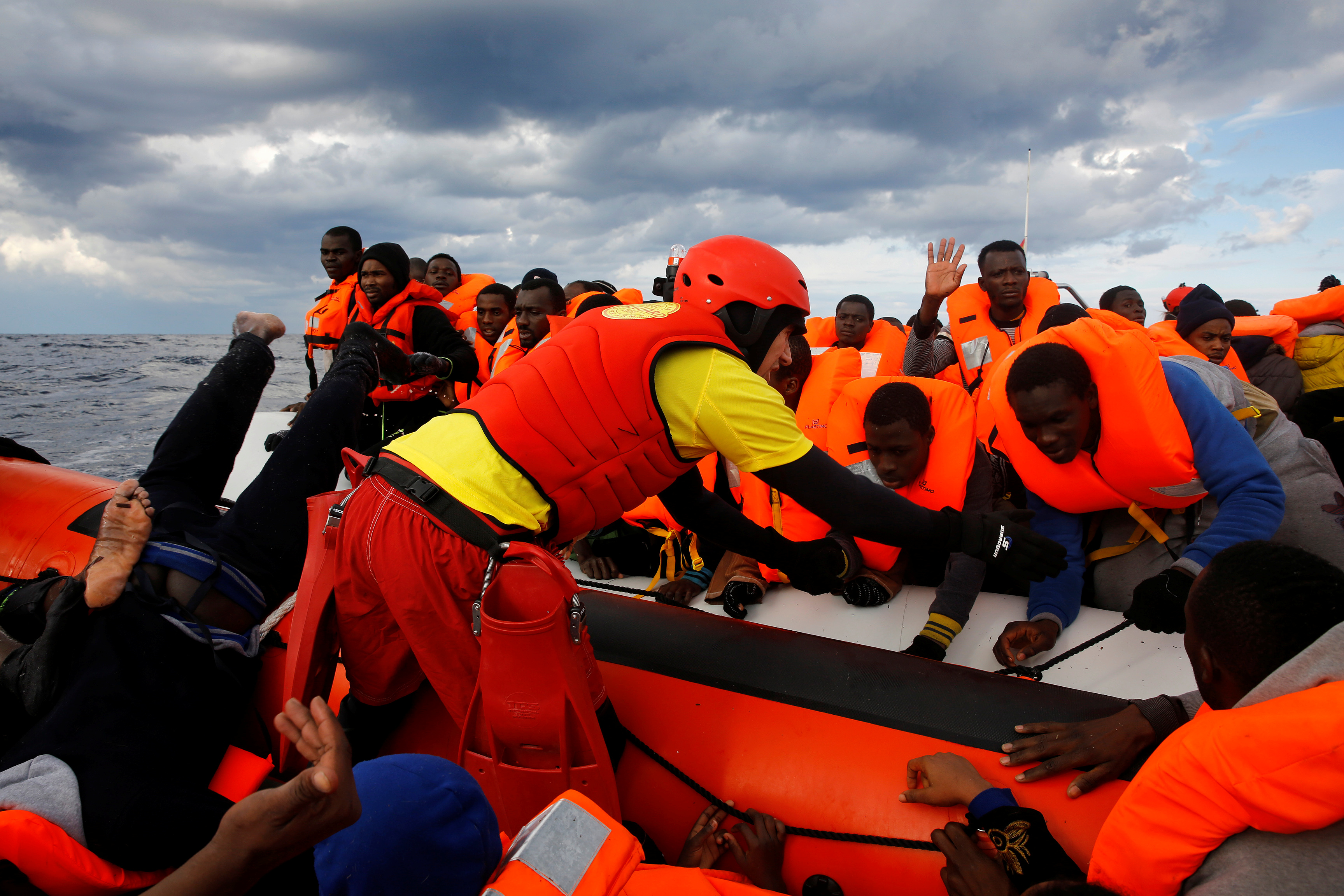 Once given life vests, the migrants are helped aboard a rescue craft that will take them to a larger boat. Photo by Yannis Behrakis/Reuters
