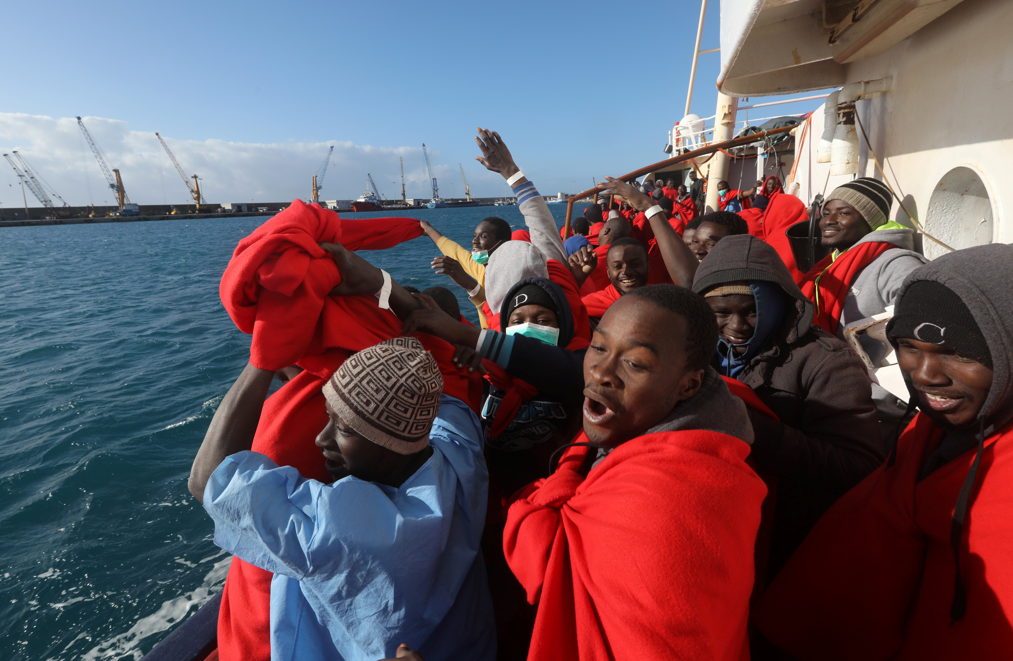 Migrants cheer as they approach the port in Sicily after their harrowing journey. Photo by Yannis Behrakis/Reuters