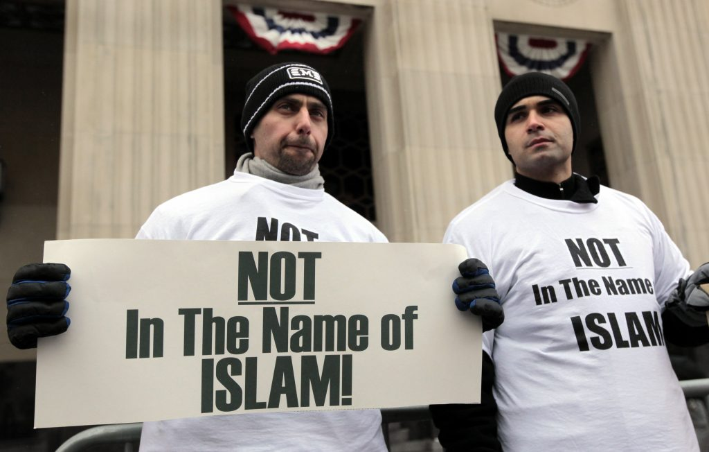 Arab-Americans Haider Koussan (L) and Ali Sayed hold signs as they join a demonstration against terrorism in front of the federal court building in Detroit, Michigan in 2010. Then, Umar Farouk Abdulmutallab was accused of attempting to blow up a Detroit-bound jetliner. Photo by Rebecca Cook/Reuters