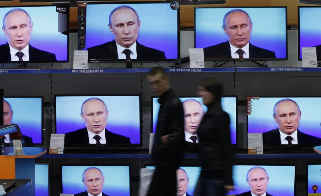 Russian President Vladimir Putin participates in a live nationwide phone-in, as seen at an electronics store in Russia's Siberian city of Krasnoyarsk on April 17, 2014. Photo by Ilya Naymushin/Reuters