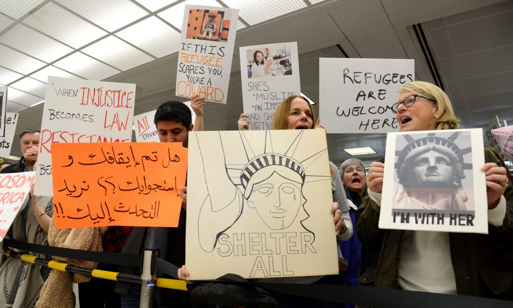 "President Donald Trump's executive order prompted spontaneous protests at airports, lawyers among the crowd offering free help. The sign in Arabic reads ""Have you been stopped and questioned, we would like to talk to you, to assist with a lawyer."" Photo by Mike Theiler/Reuters"