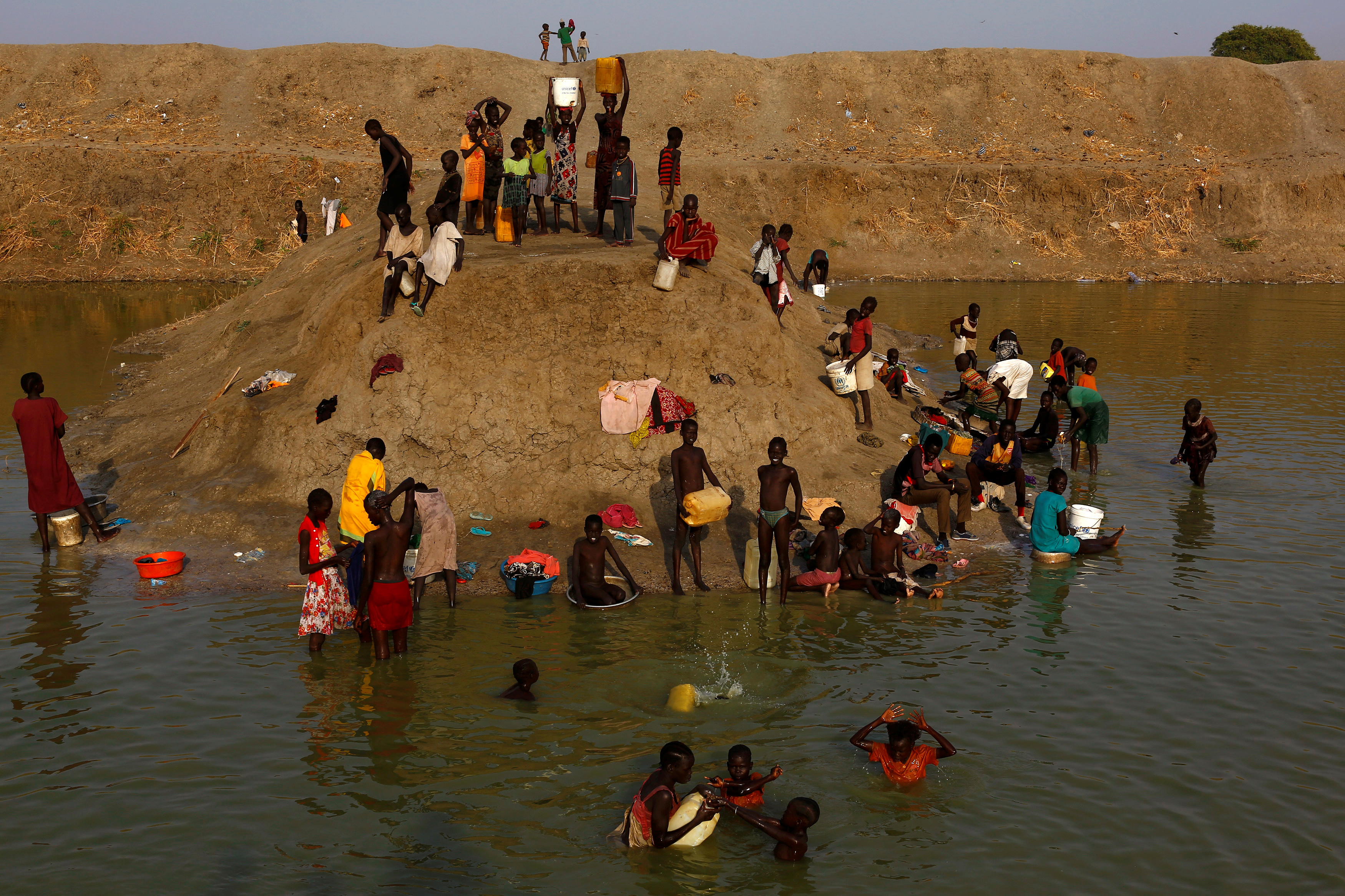 Internally displaced people wash and collect water in a reservoir in the U.N. Mission in South Sudan protected site near Bentiu in northern South Sudan. Photo by Siegfried Modola/Reuters