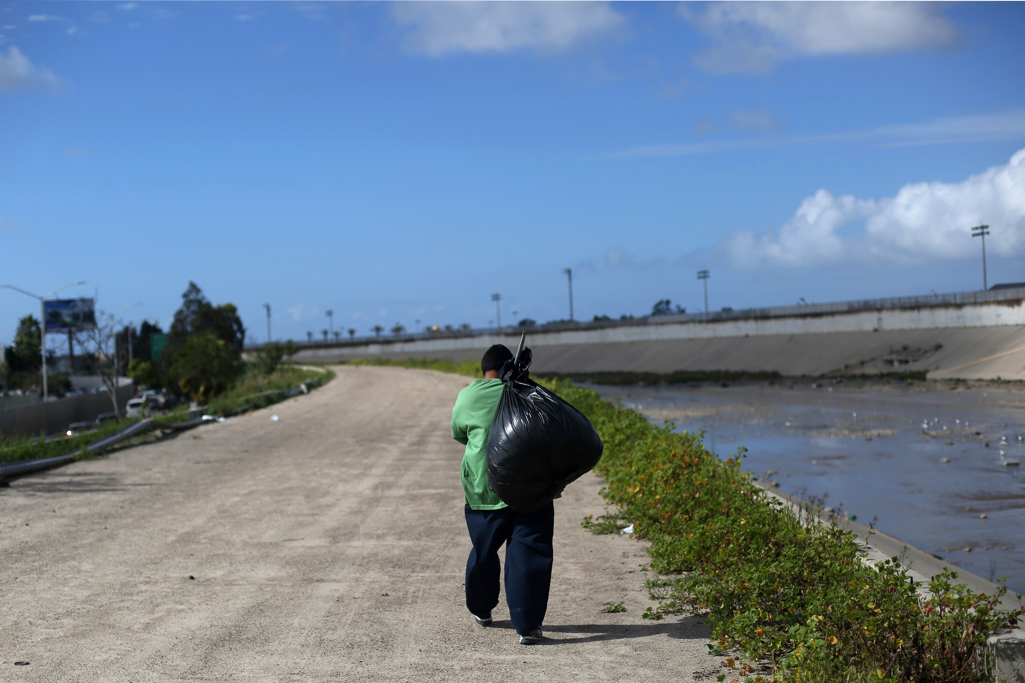 A Mexican who was recently deported from the U.S. carries a black bag Feb. 22 next to the Tijuana river, in Tijuana, Mexico. REUTERS/Edgard Garrido - RTSZWEE