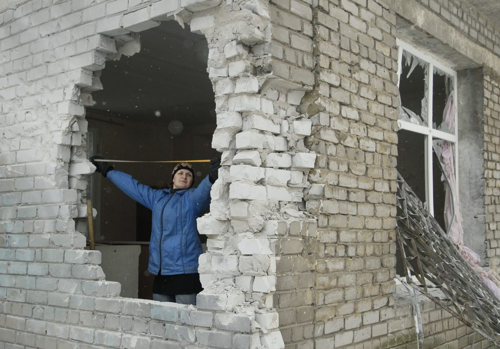 A woman inspects a hole in a damaged building, which was caused by shelling, in the rebel-held city of Donetsk, Ukraine, on Feb. 3. Photo by Alexander Ermochenko/Reuters