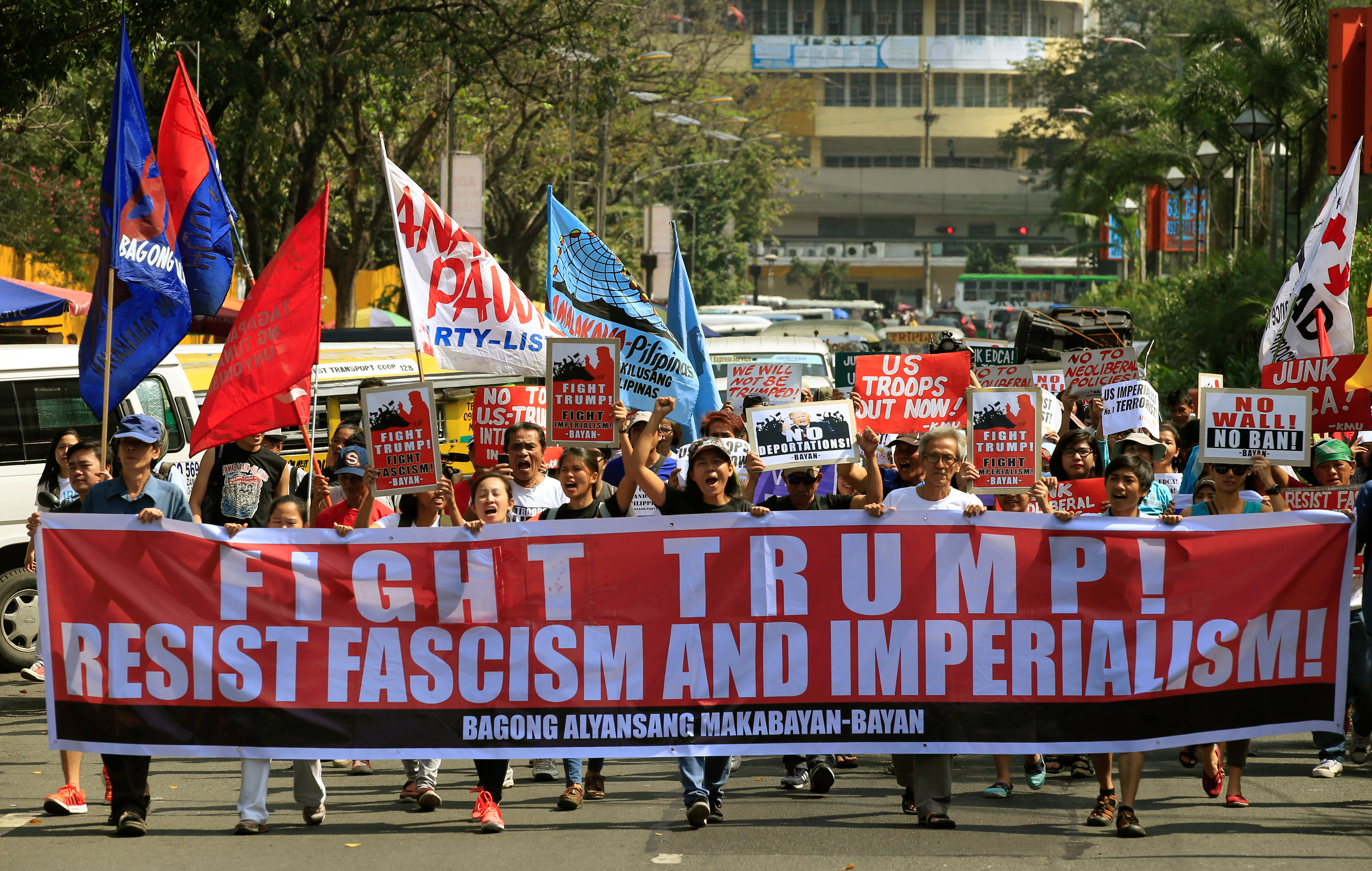 Filipino activists hold banner and placards while marching towards the U.S. embassy during a protest against U.S. President Donald Trump's immigration policies, in metro Manila February 4, 2017. REUTERS/Romeo Ranoco - RTX2ZKKK