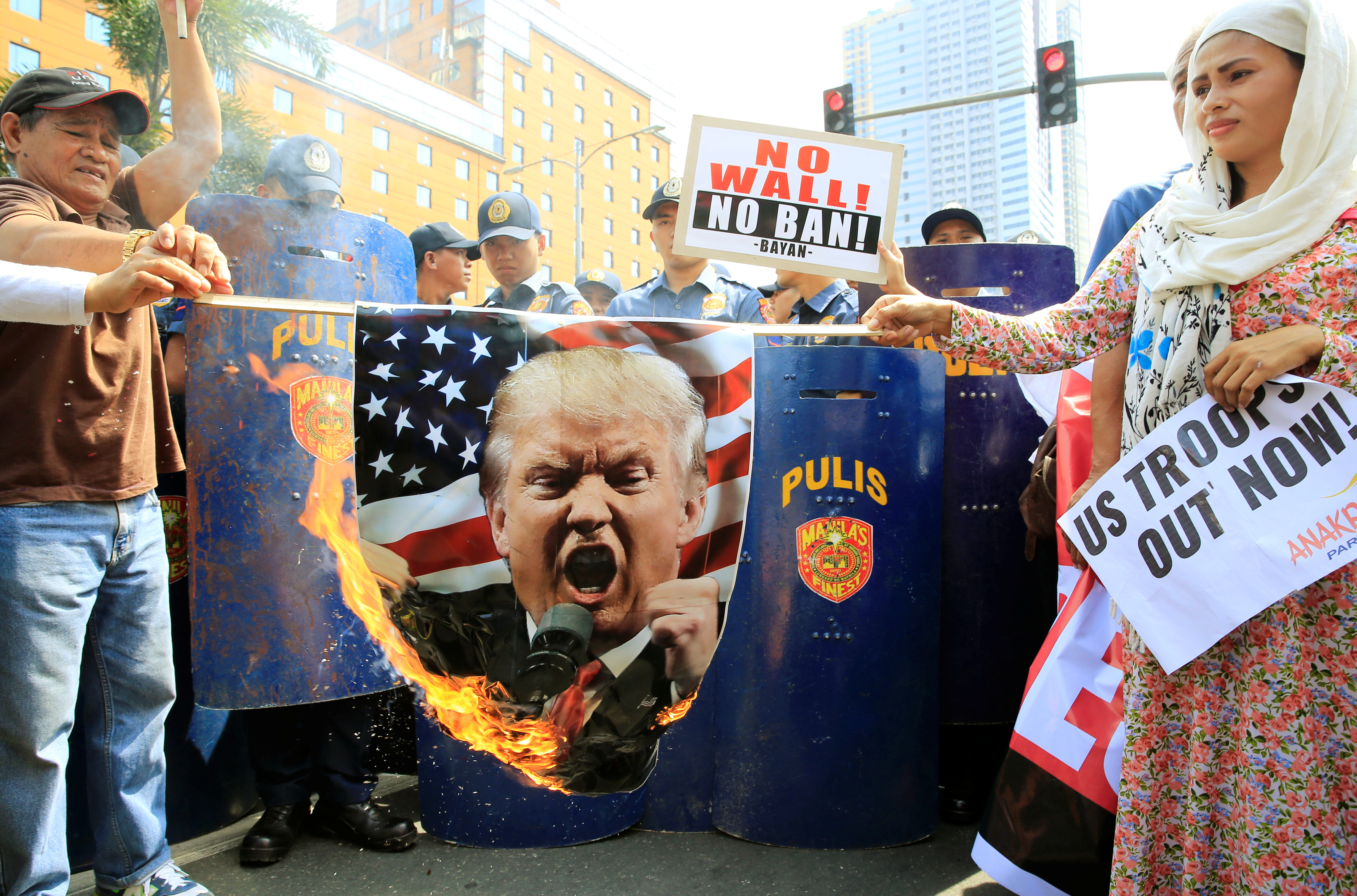 Filipino activists burn a portrait of U.S. President Donald Trump during a protest against U.S. immigration policies outside the U.S. embassy in metro Manila, Philippines February 4, 2017. REUTERS/Romeo Ranoco - RTX2ZKKL