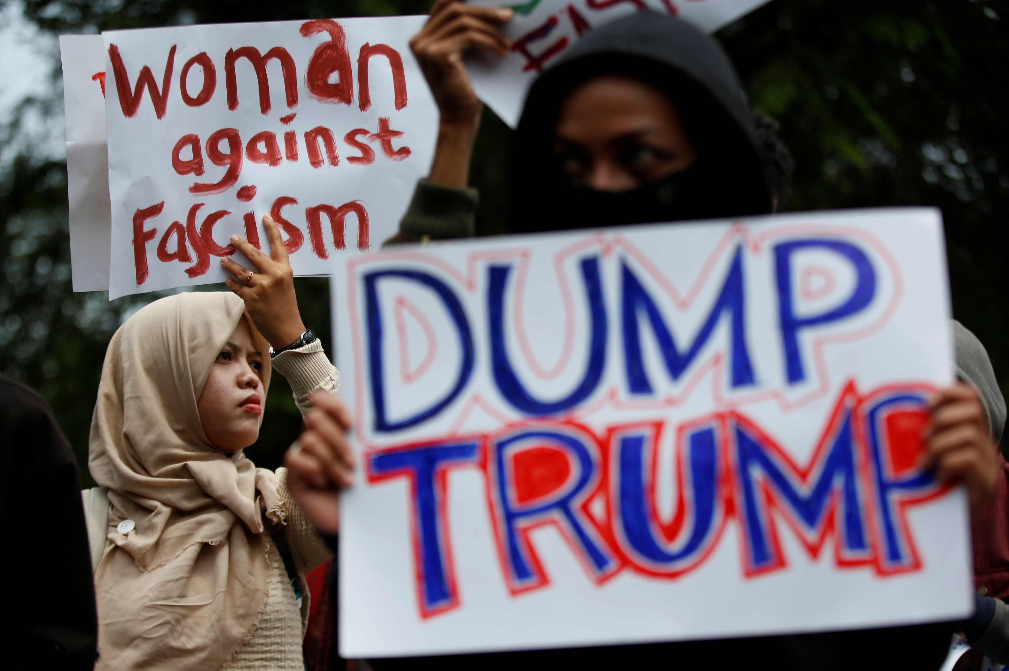 Activist hold placards as they protest against U.S. President Donald Trump's recent policies, outside the U.S. embassy in Jakarta, Indonesia, February 4, 2017. REUTERS/Darren Whiteside - RTX2ZKM1