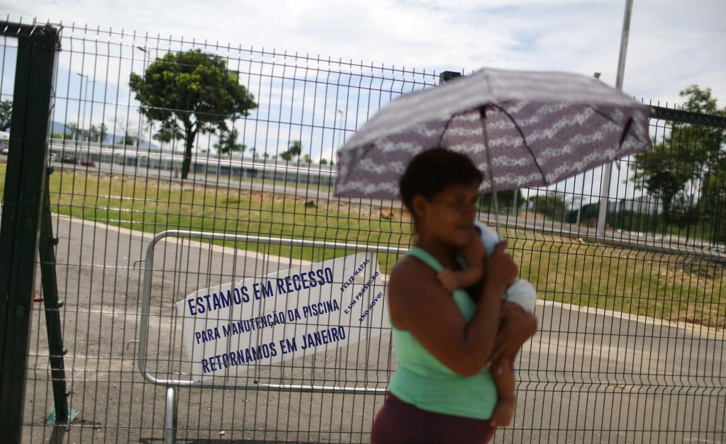"A woman carries a baby in front of the Deodoro Sports Complex, which was used for the Rio 2016 Olympic Games, in Rio de Janeiro, Brazil, February 7, 2017. The clapboard reads: "" We are in recess for maintenance of the pool, we will return in January. Merry Christmas and Happy new year"". Picture taken on Feb. 7, 2017. Photo by Pilar Olivares/Reuters"