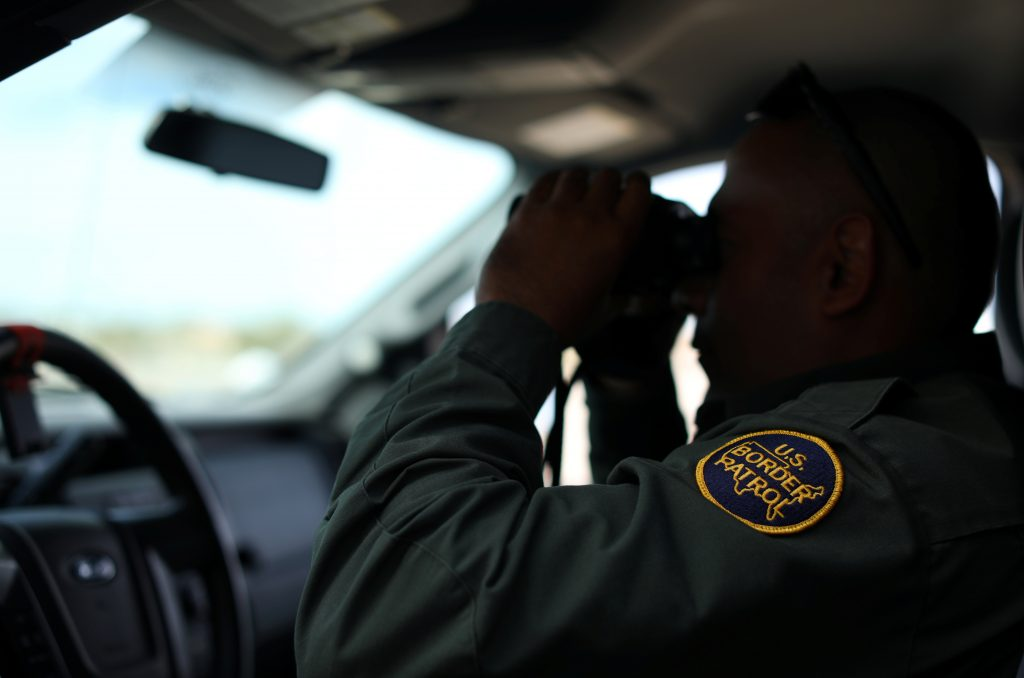 A U.S. border patrol agent keeps watch along the fence next to the Mexican border in Calexico, California. Photo by Mike B...