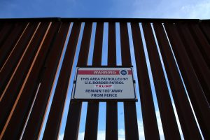 A Donald Trump for President campaign sticker is attached to a U.S. Customs sign hanging on the border fence between Mexico and the United States near Calexico, California. Photo by Mike Blake/Reuters