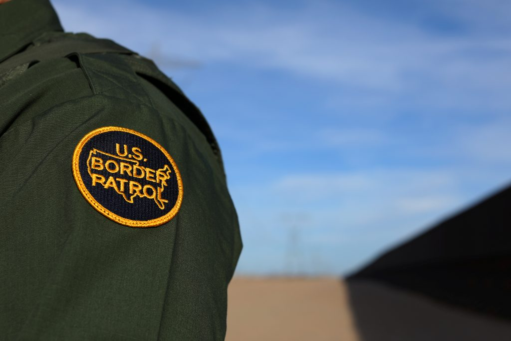 A U.S. border patrol agent walks along the border fence separating Mexico from the United States near Calexico, California...
