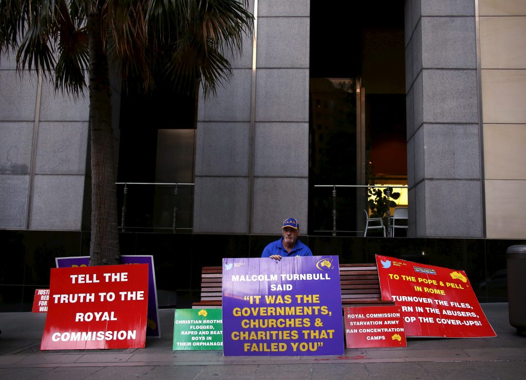 A man who claims to have been sexually abused by the Catholic Church holds a placard last year as he stands outside the venue for Australia's Royal Commission into Institutional Response to Child Sexual Abuse in Sydney, Australia. Photo by   REUTERS/David Gray.