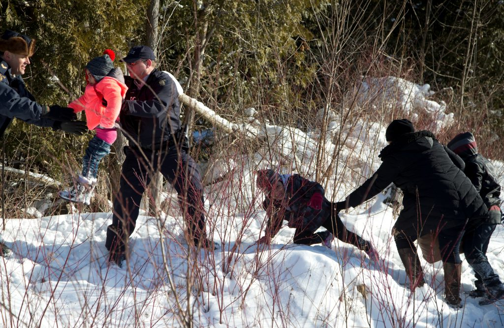Royal Canadian Mounted Police (RCMP) officers assist a child from a family that claimed to be from Sudan as they walk across the U.S.-Canada border into Hemmingford, Canada, from Champlain in New York. Photo by REUTERS/Christinne Muschi.