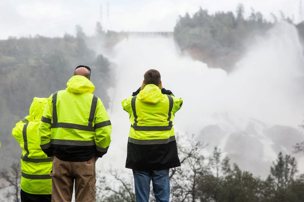California Department of Water Resources personnel monitor water flowing through a damaged spillway on the Oroville Dam in Oroville, California, U.S., on February 10, 2017. - RTX30IIQ