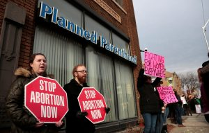 Anti-abortion activists (L) rally next to supporters of Planned Parenthood outside a Planned Parenthood clinic, Feb. 11 in Detroit, Michigan. Photo by Rebecca Cook/Reuters