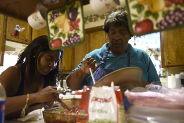 Sharissa Derricott helps her mother Cheryl prepare dinner at her parents' home in Lawton Oklahoma. Derricott says she took Lupron from age 5 to 12 to shut down early puberty. At 30, she's among the first patients who took the drug – even before it was approved for pediatric use. (Nick Oxford/for KHN)