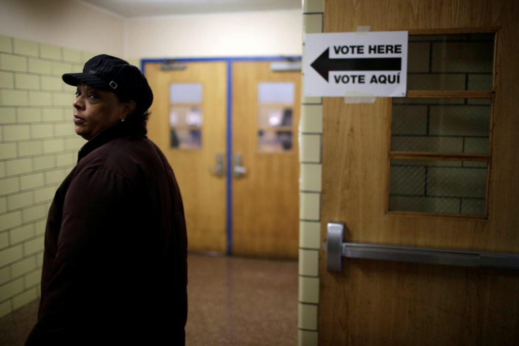 A voter casts his ballot behind a ballot booth during the U.S. presidential election at a polling station in the Bronx Borough of New York.