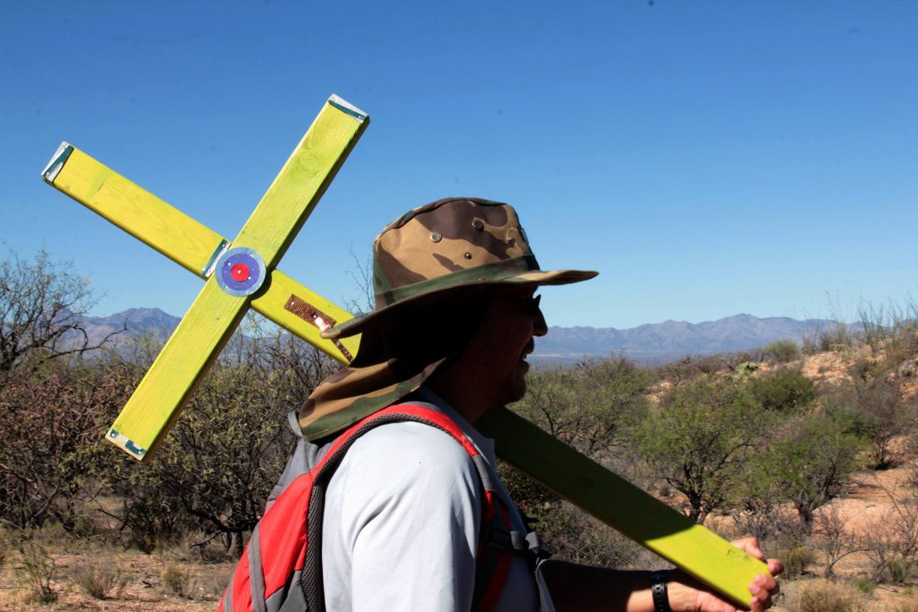 Brother Andres Rivera, a volunteer with the Tucson Samaritans, carries a handmade cross in Arizona's Sonoran Desert. Photo by Joshua Barajas.