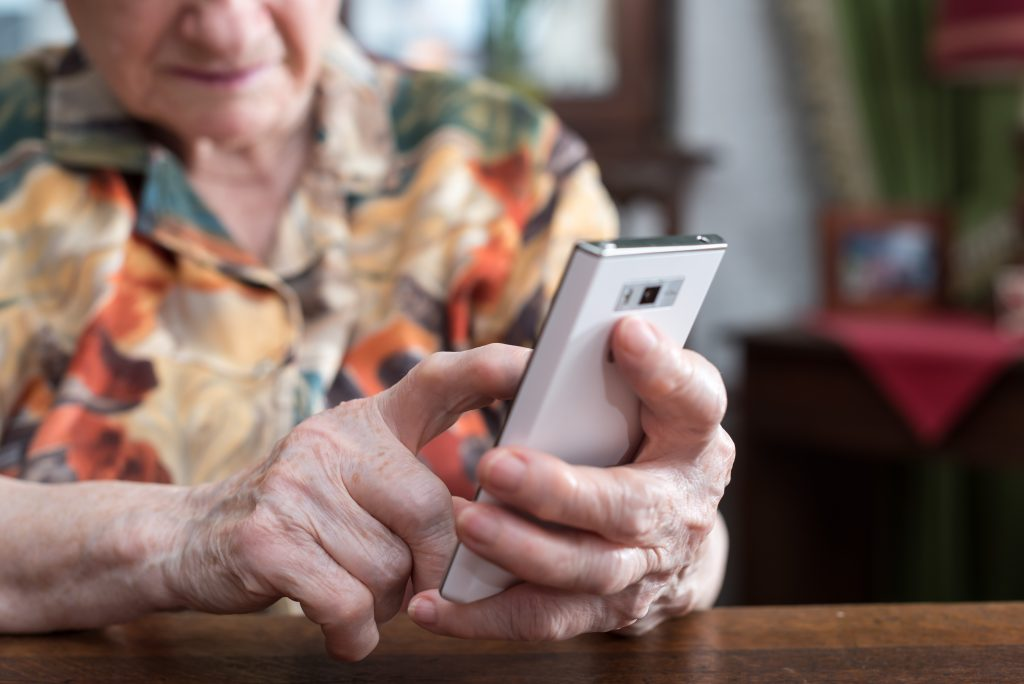 An elderly woman uses smartphone at home. Photo by Adobe.